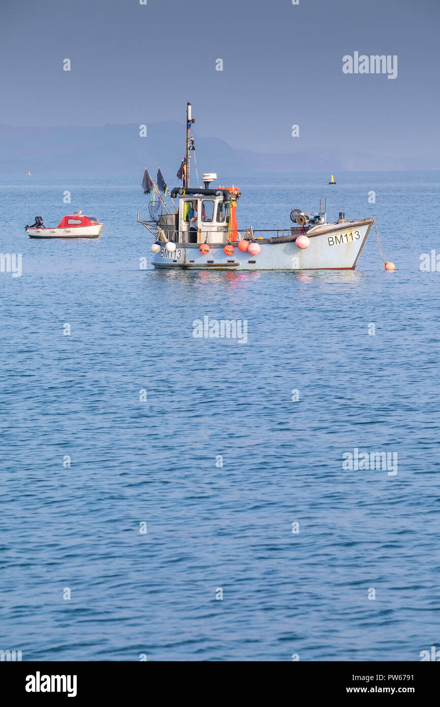 A fishing boat a small motor boat anchored off the coast of Dorset. - Stock Image