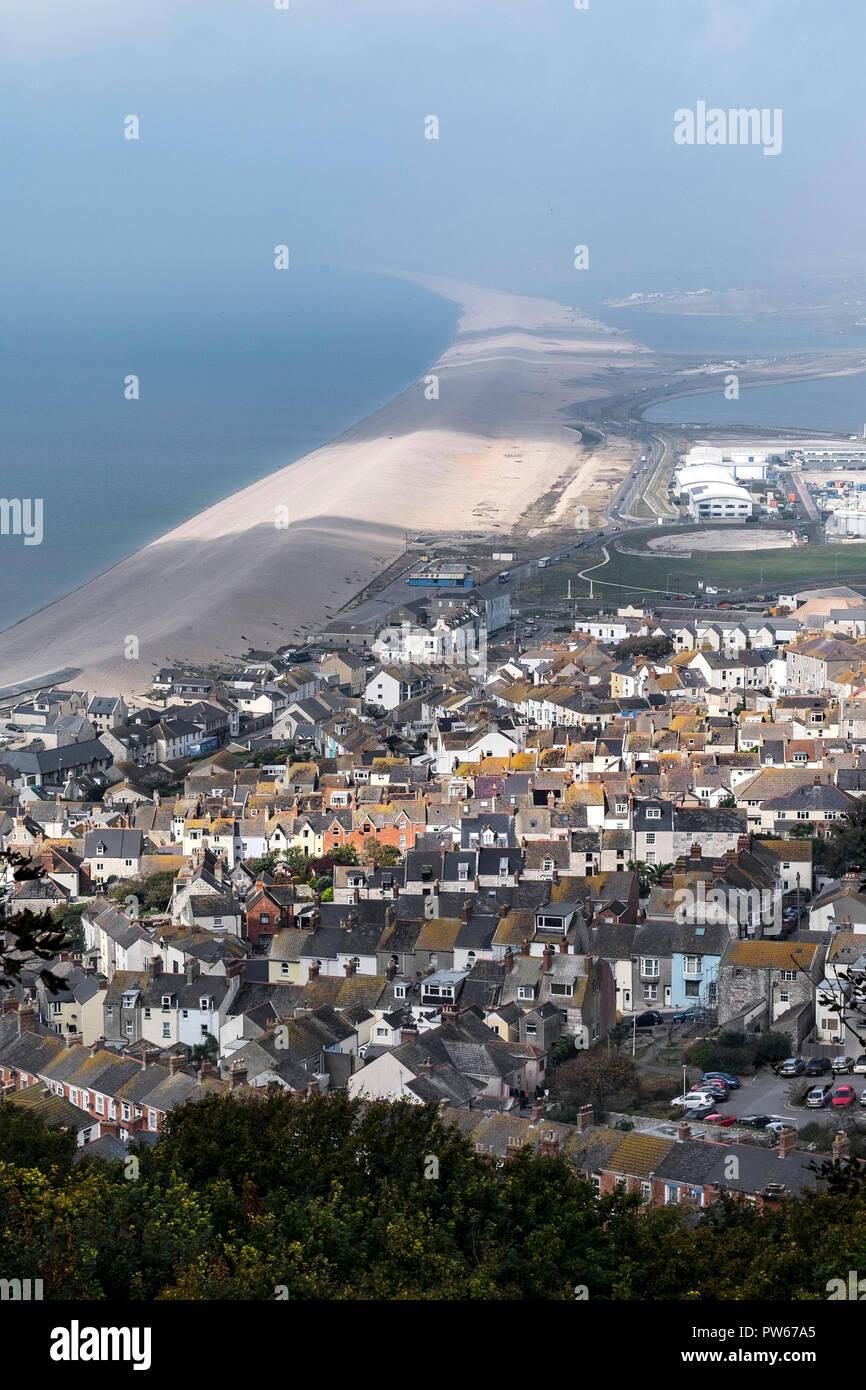 Chesil Beach and houses on the Isle of Portland in Dorset in the UK. - Stock Image