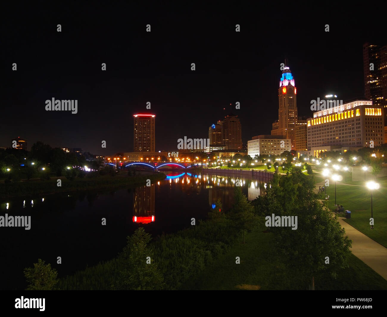 COLUMBUS, OHIO - JULY 15, 2018: A night view of John W. Galbreath Bicentennial Park and the city skyline of Columbus, Ohio reflecting on the river. - Stock Image