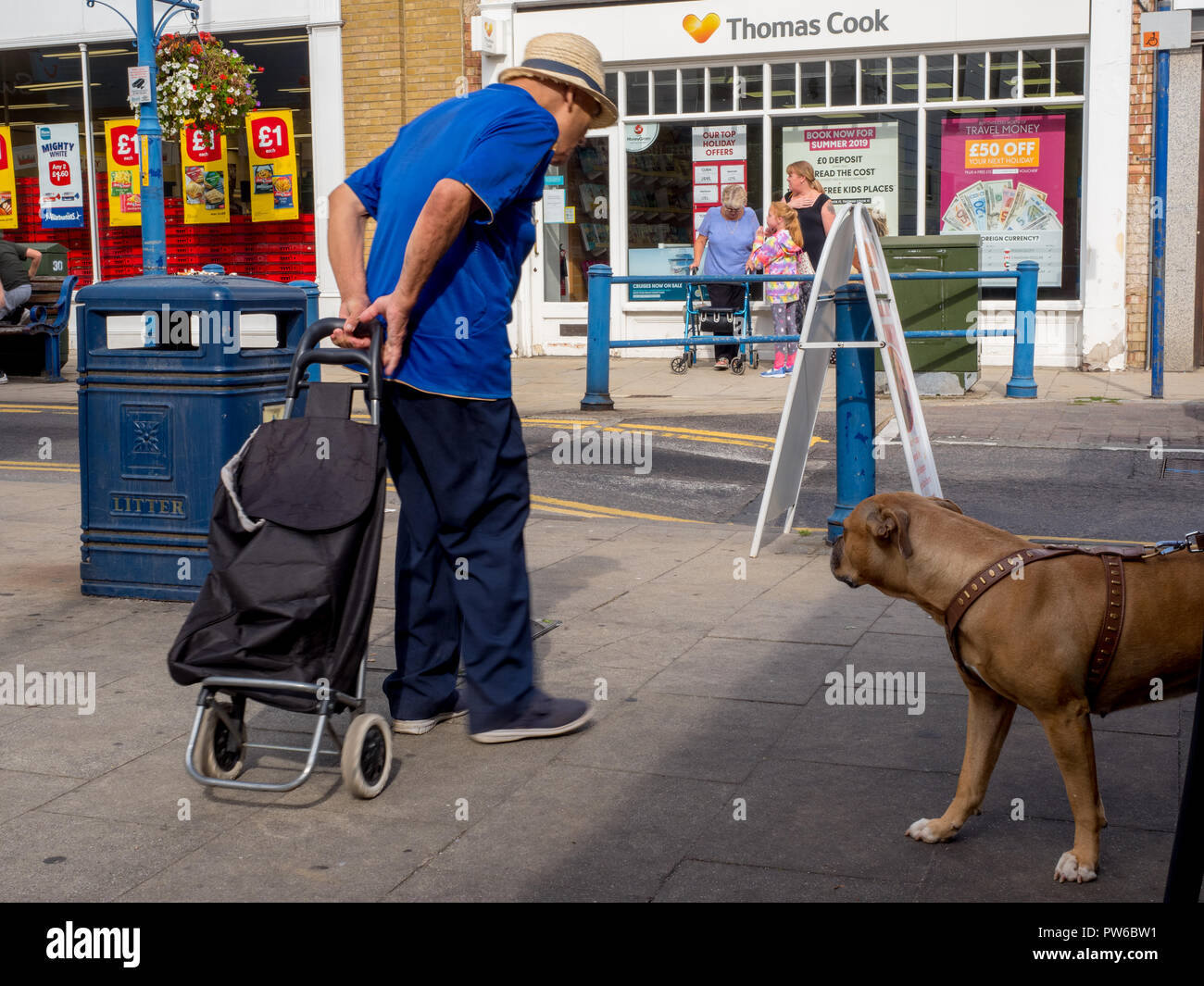 An old man with his shopping trolley passes a dog on Sheerness High