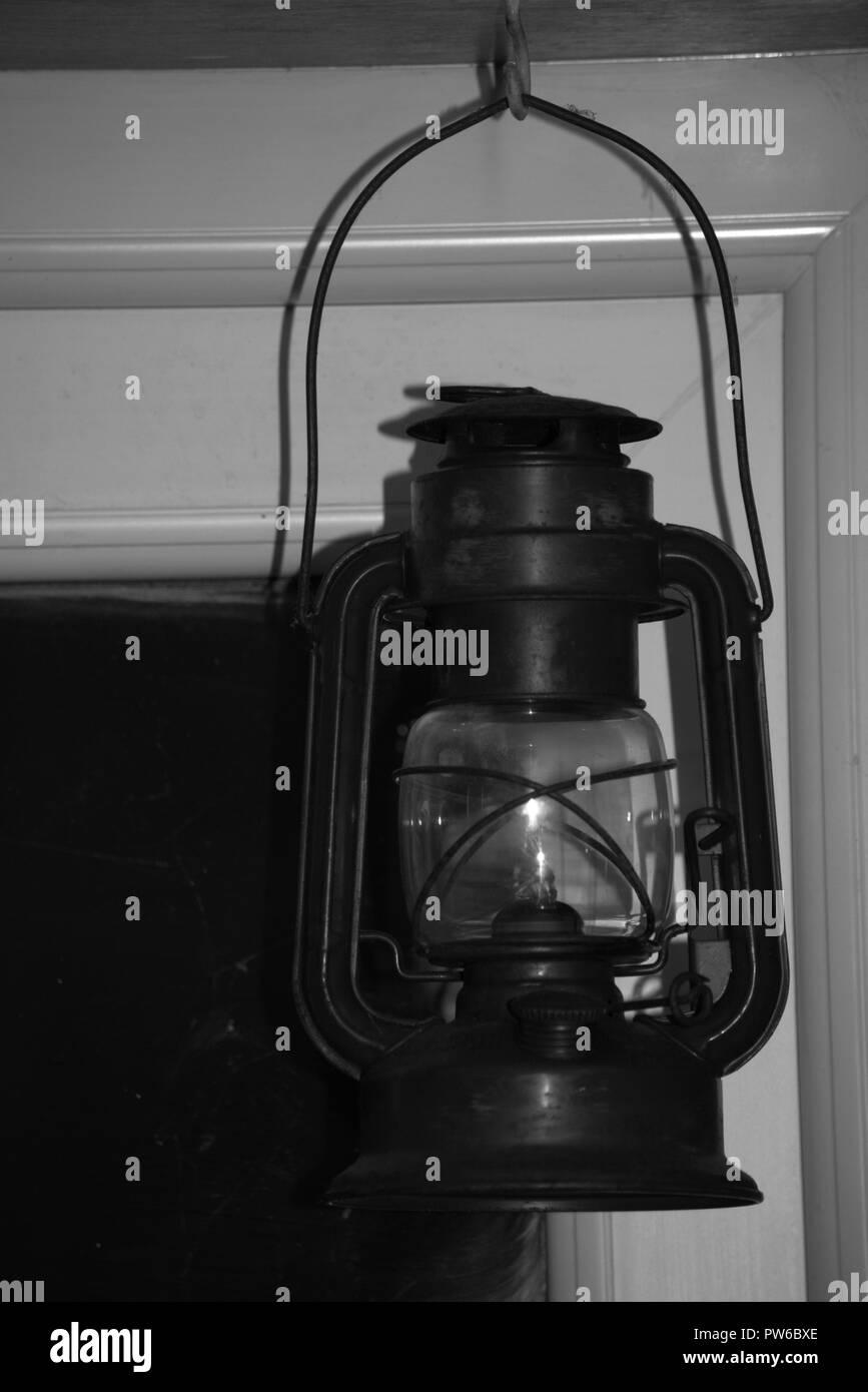 Kerosene or hurricane lamp framed in a doorway, black and white - Stock Image