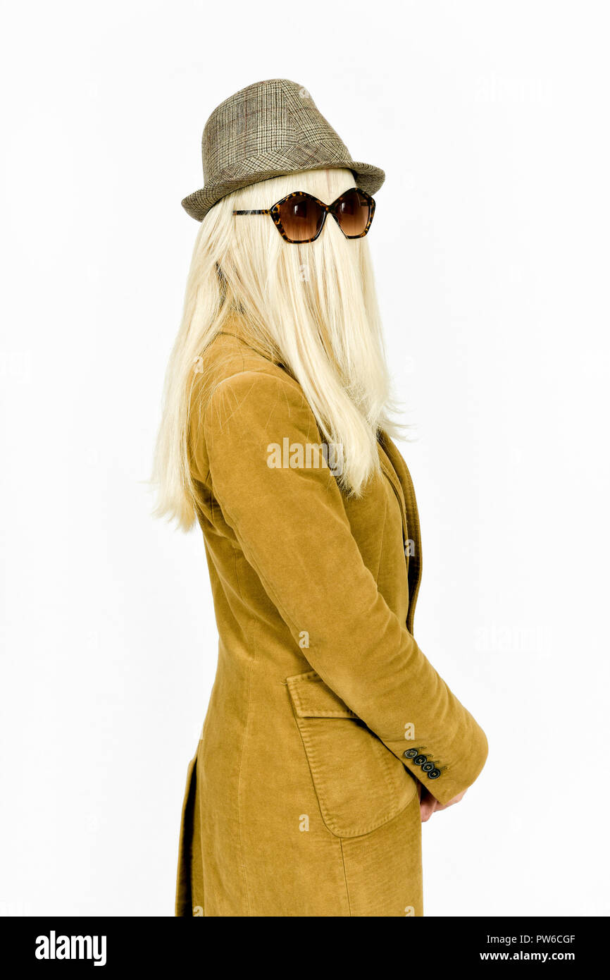 Fun image of woman with long blonde hair covering face and sun glasses playing dress up for Halloween as Cousin Itt - Stock Image