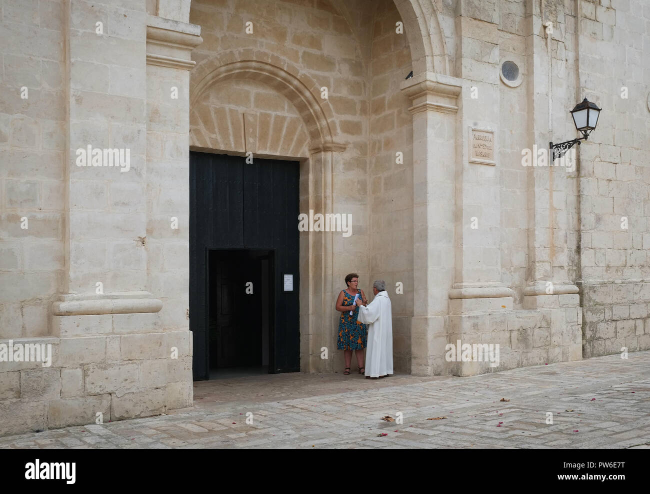 A Catholic priest talks to a member of the congregation after Sunday Mass at Parroquia De Nuestra Señora Del Rosario, Es Castell, Menorca, Spain - Stock Image