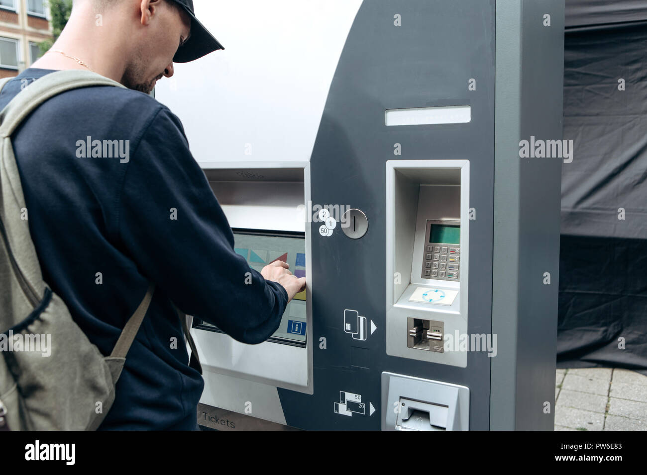 Tourist buys tickets for land or underground transport in Germany. Independent purchase of tickets for the tram, bus and train in a modern street machine. - Stock Image