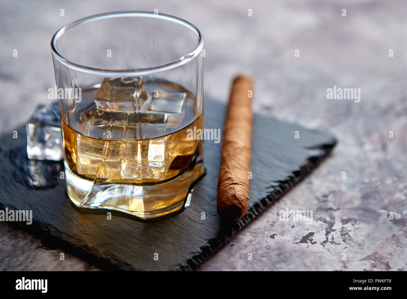 Glass of whiskey with ice cubes and cigar - Stock Image
