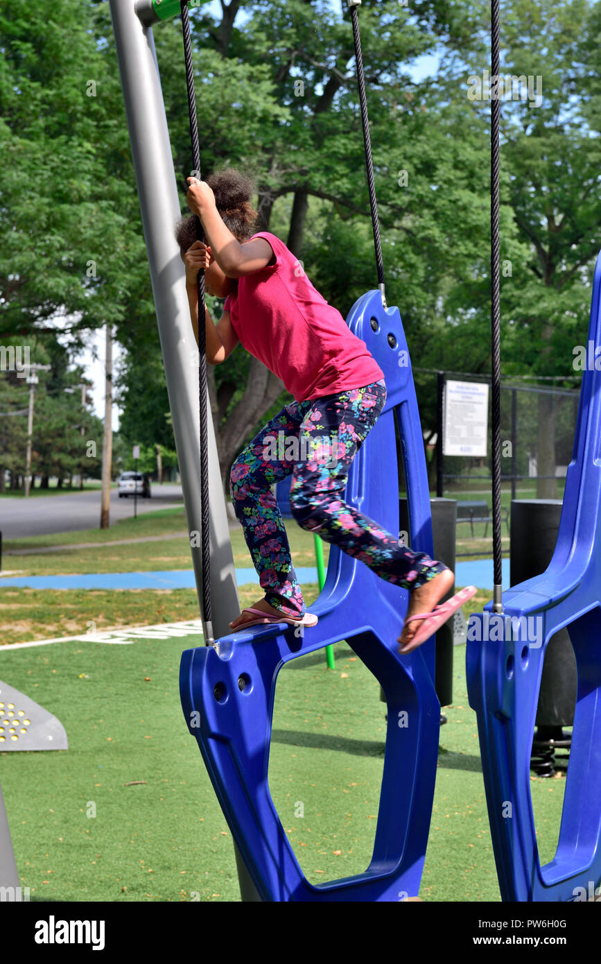 Young girl climbing on play equipment in public park, Rochester, New York, USA - Stock Image