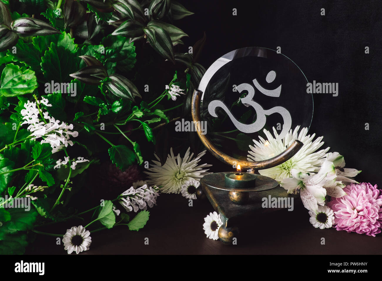 Green Candle on Om Altar with Mixed Flowers and Foliage Stock Photo
