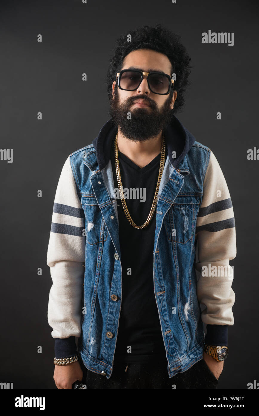 Thoughtful bearded young man with gold chain and jeans sweater and sunglasses. Man holding a mod. - Stock Image