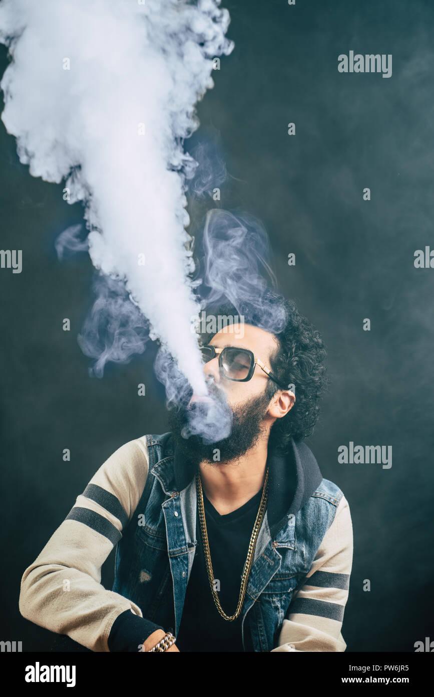 Young man with beard vaping an electronic cigarette upwards. Vaper hipster smoke vaporizer. Black background - Stock Image