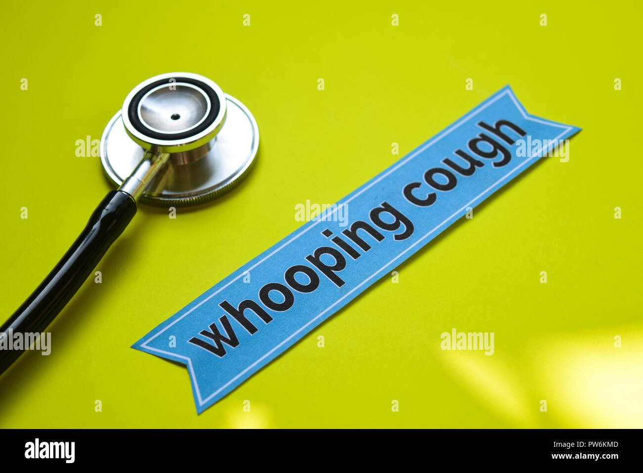 whooping cough with stethoscope concept inspiration on yellow background - Stock Image