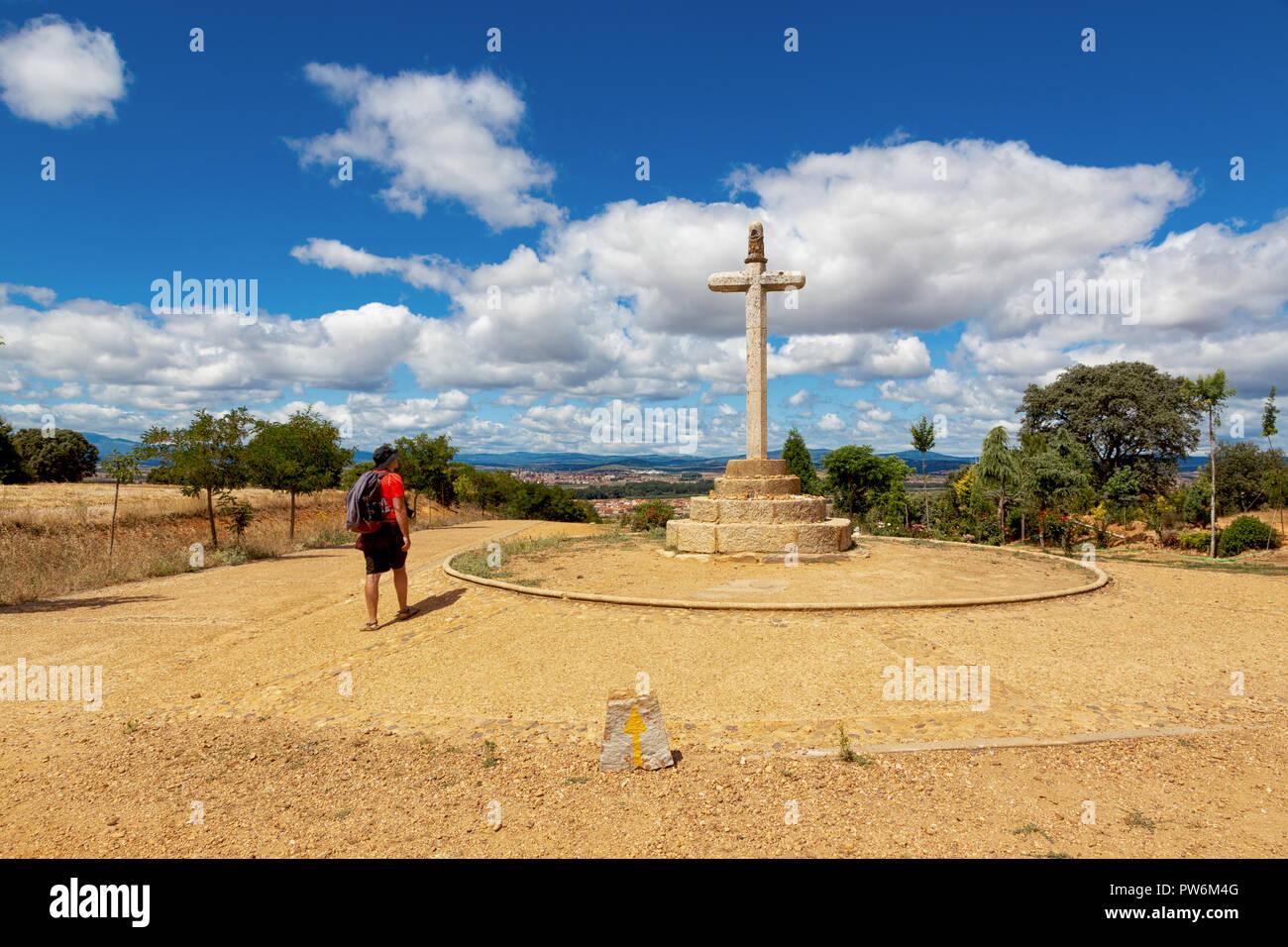 Camino de Santiago (Spain) - The Santo Toribio stone cross and a pilgrim walking along the way of St.James, near Astorga - Stock Image