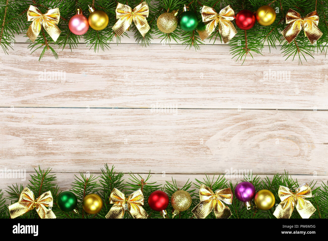 Christmas frame made of fir branches decorated with balls and bows on a light wooden background - Stock Image