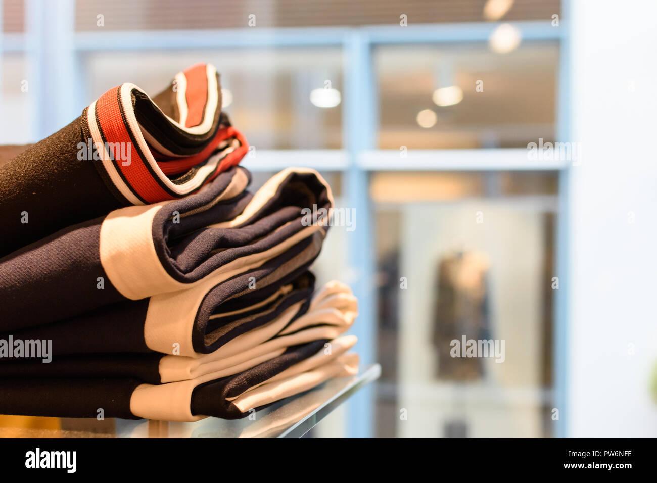 Kleider gestapelt im verkaufsraum - Stock Image