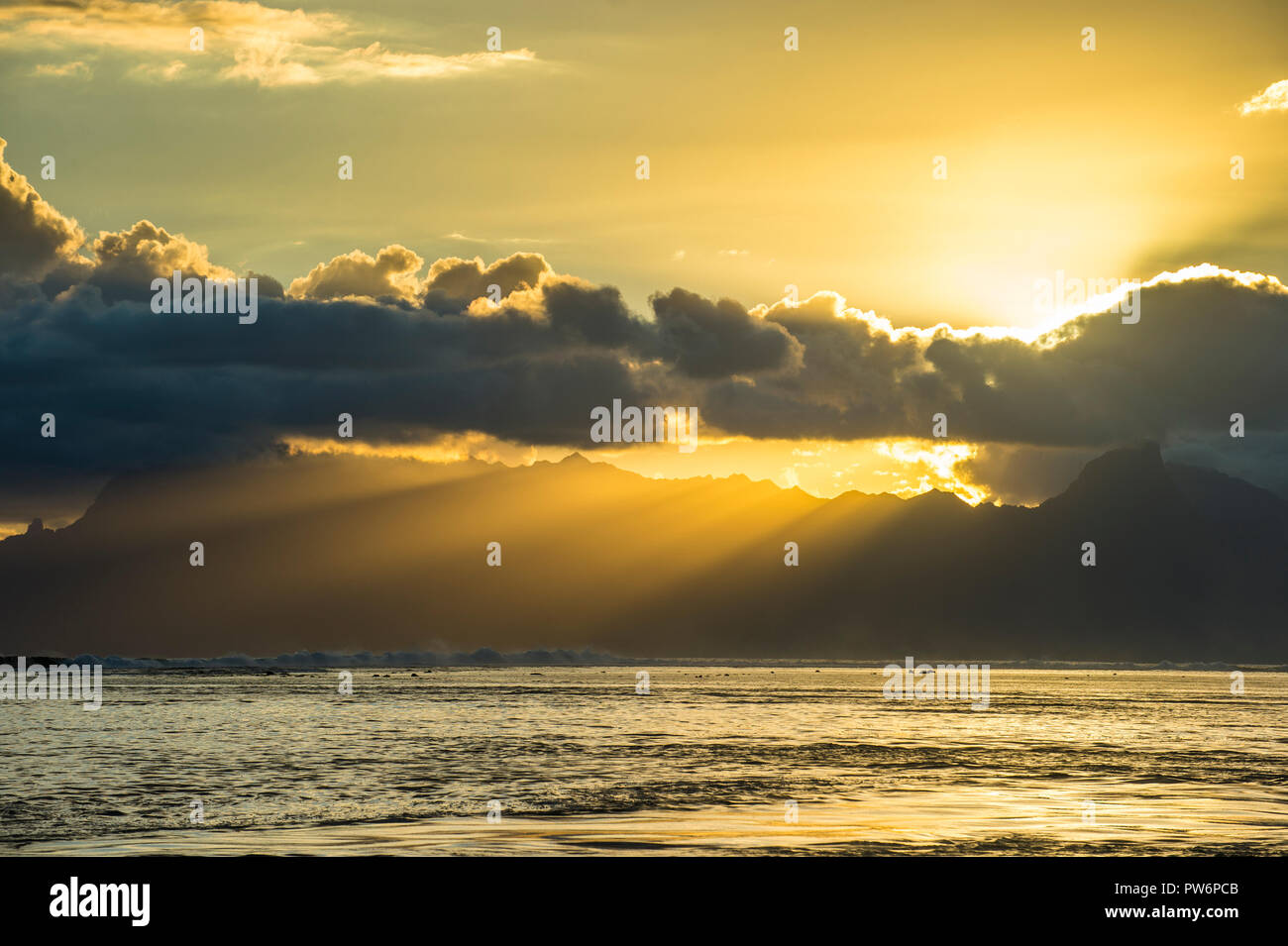 Sun rays breakig through the clouds over Moorea, Papeete, Tahiti - Stock Image