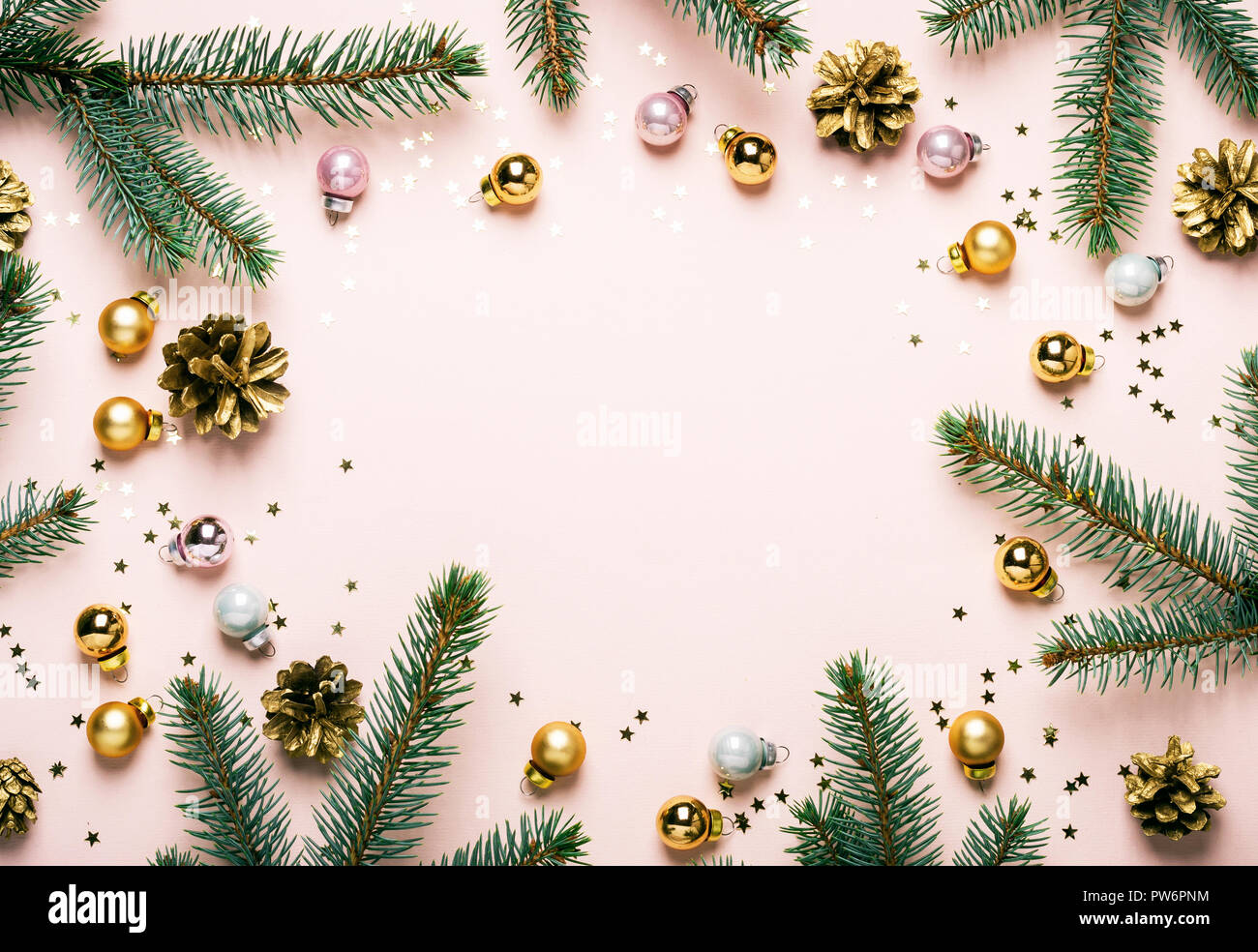 Pastel Pink Christmas Festive frame of fir branches, golden balls and confetti. Stock Photo