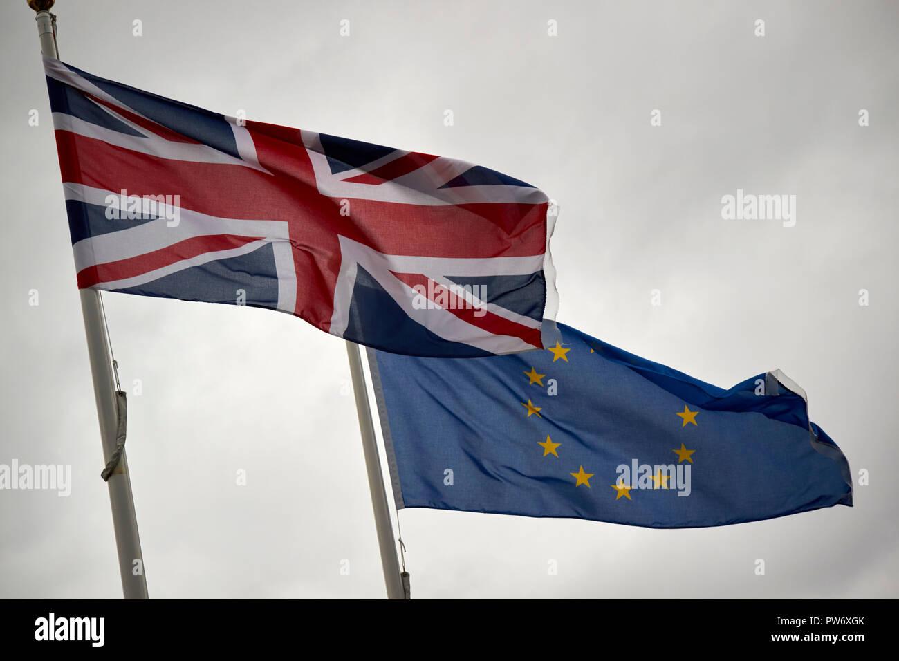 british uk union flag and eu flag flying in dark stormy sky england uk - Stock Image