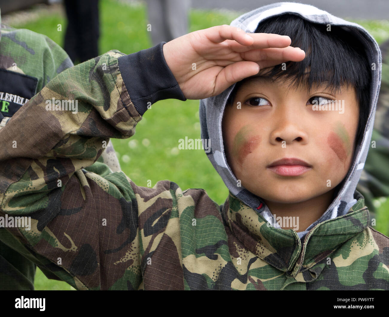 Close up photo of Asian Boy saluting in camouflage uniform. - Stock Image