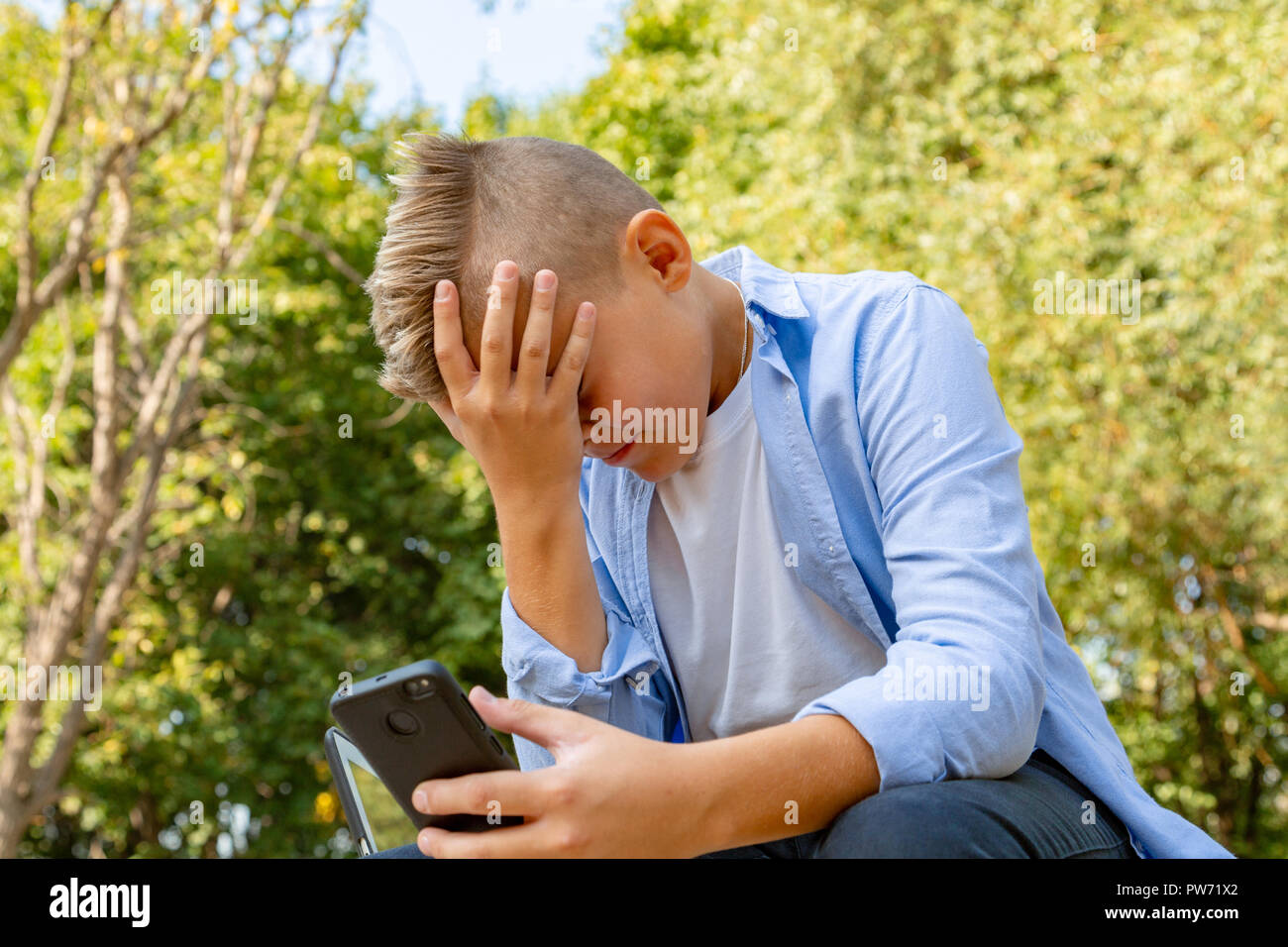childhood, augmented reality, technology and people concept - boy with upset face looks into the smartphone outdoors at summer - Stock Image