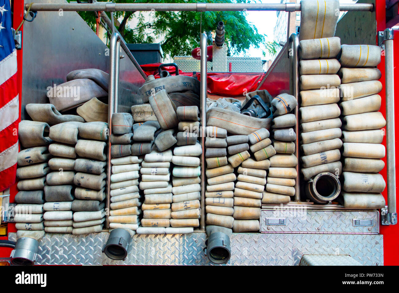 Fabric industrial strength fireman water hoses in the back of a firetruck - Stock Image