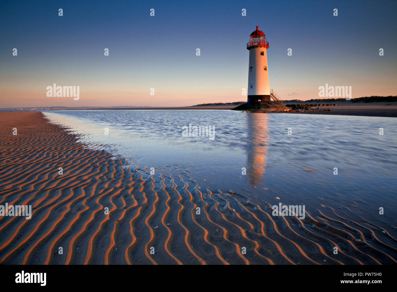 Point of Ayr lighthouse on Talacre beach, North Wales coast reflecting in a tidal pool - Stock Image