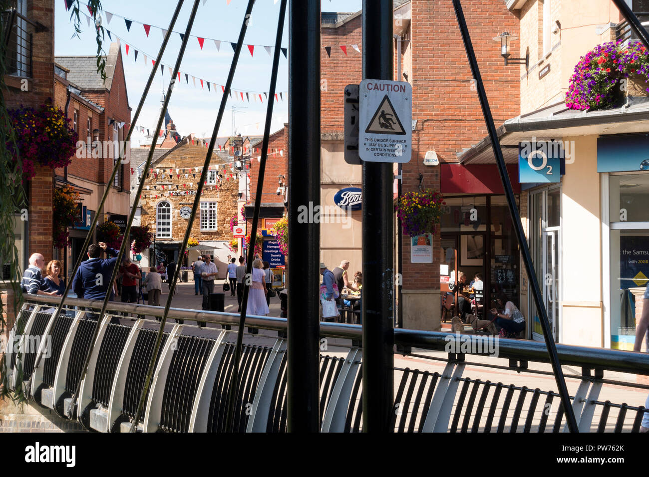 Metal bridge over River Welland and shoppers at St. Mary's Place Shopping Centre, Market Harborough, Leicestershire, England, UK - Stock Image
