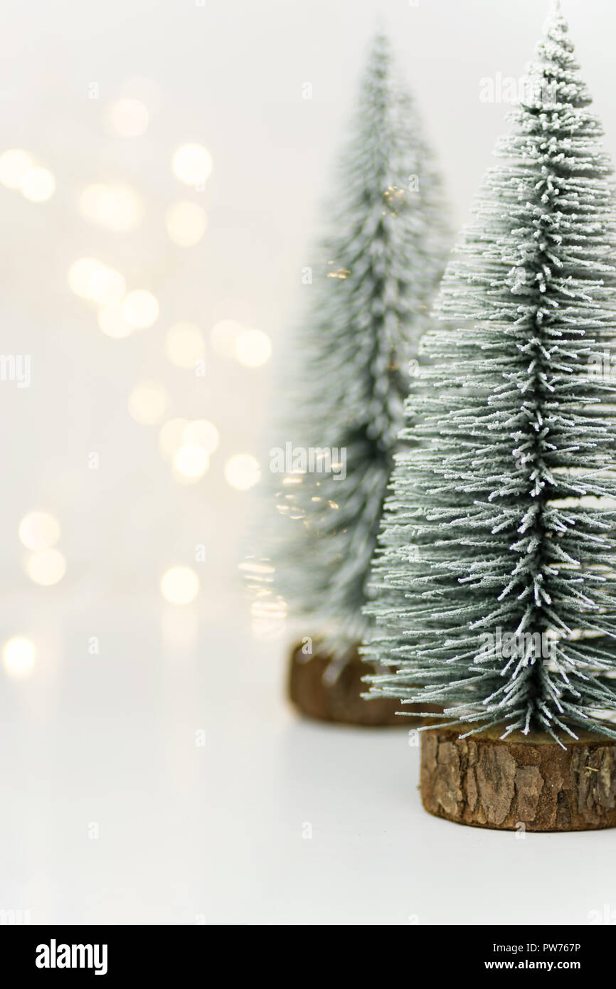 fluffy covered with snow christmas trees in forest golden bokeh garland lights white background new years holiday magic atmosphere greeting card ban