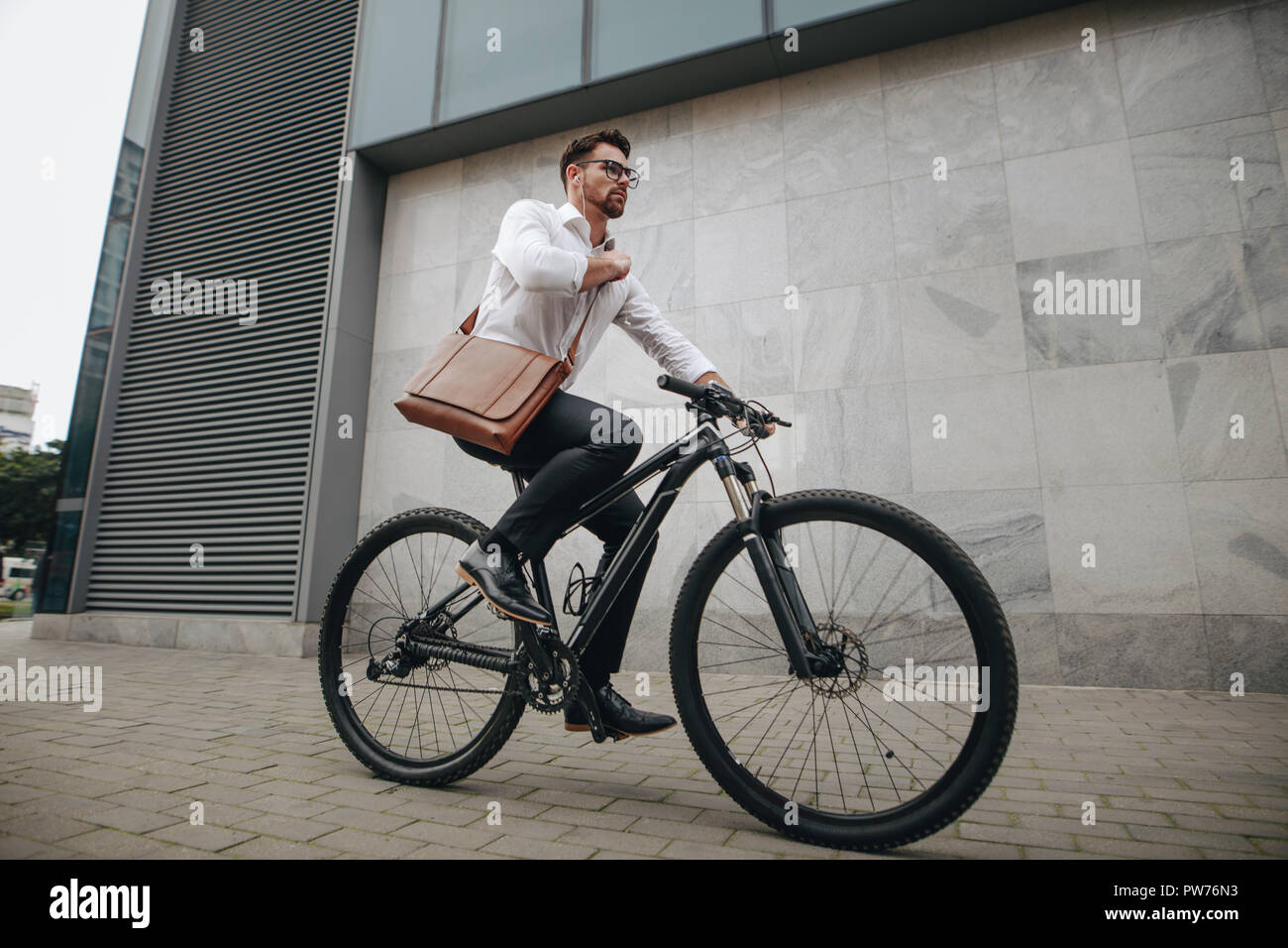 Side view of an entrepreneur commuting to office on a bike. Man wearing office bag riding a bicycle in street going to office. - Stock Image