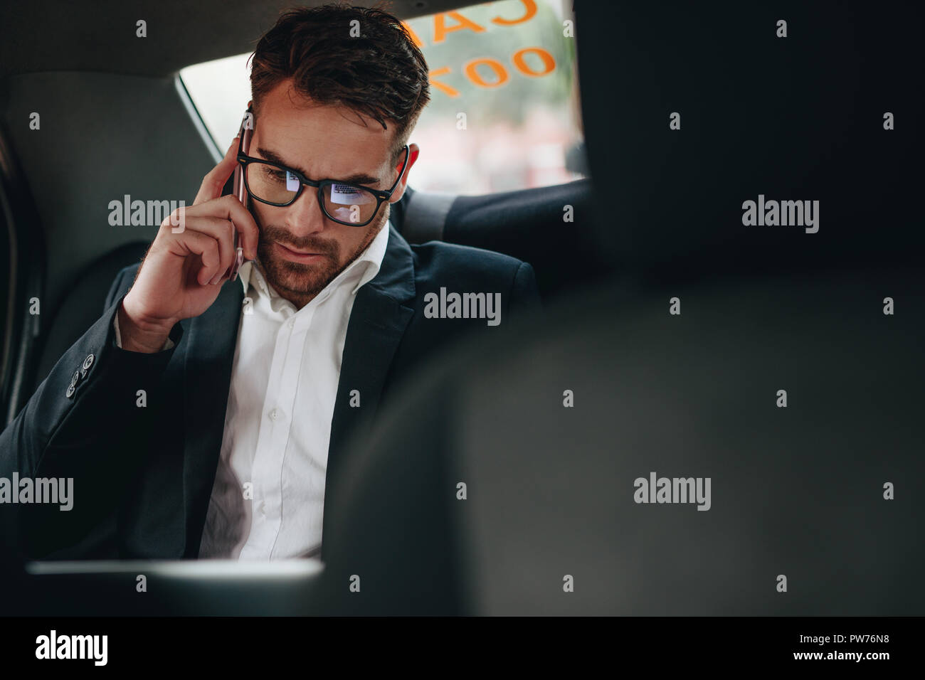 Businessman doing office work while commuting to office in a taxi. Entrepreneur managing business work on the move sitting in a car. - Stock Image