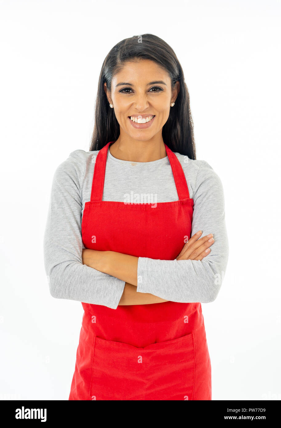 Portrait of a happy proud beautiful latin woman wearing a red apron learning to cook making thumb up gesture in cooking classes small business and hom - Stock Image