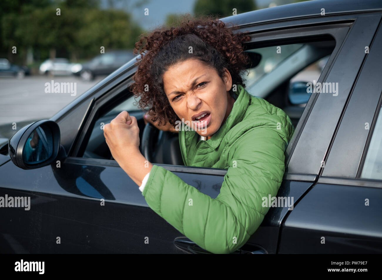 Rude black woman driver arguing and driving car - Stock Image