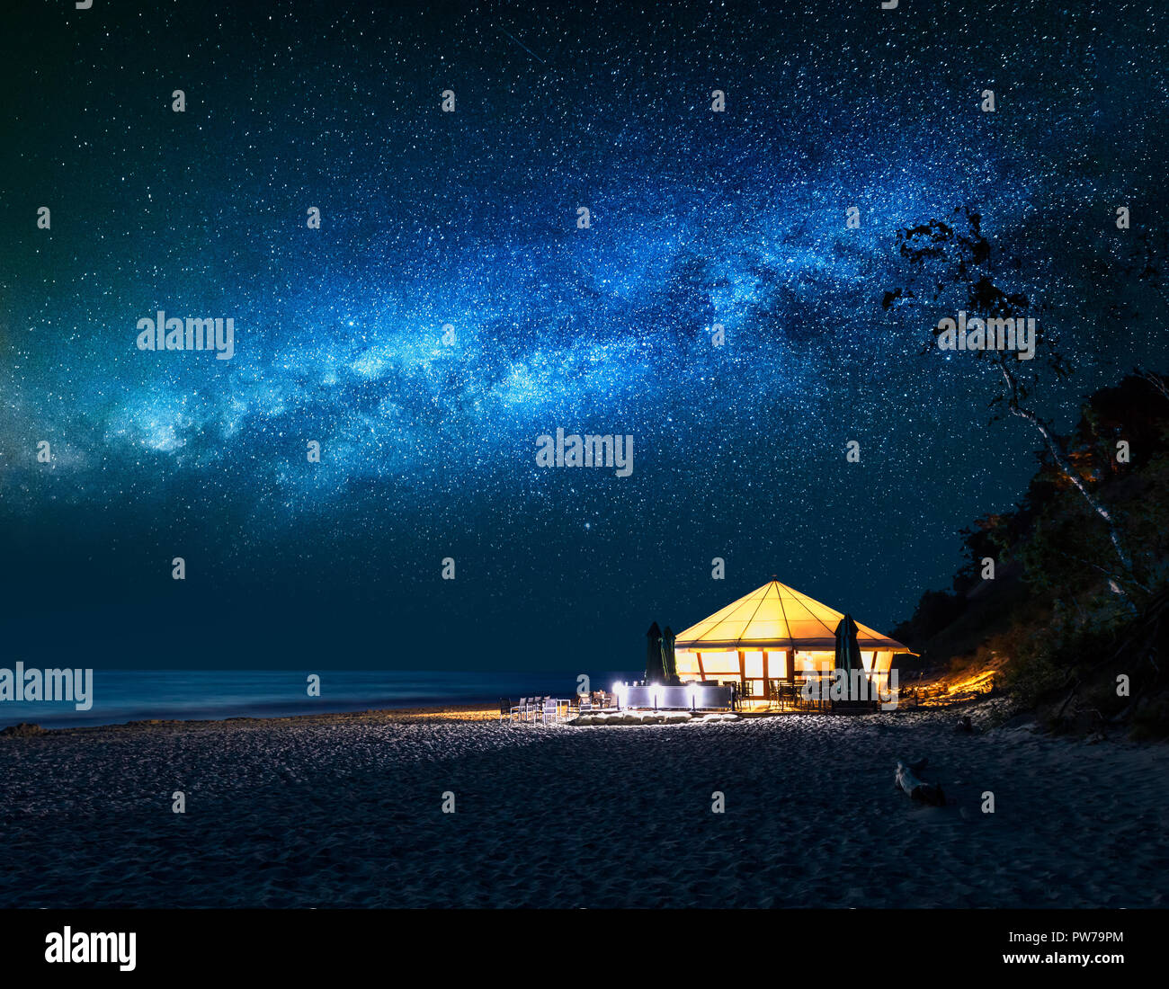 Beach with glowing tent at night with falling stars Stock Photo