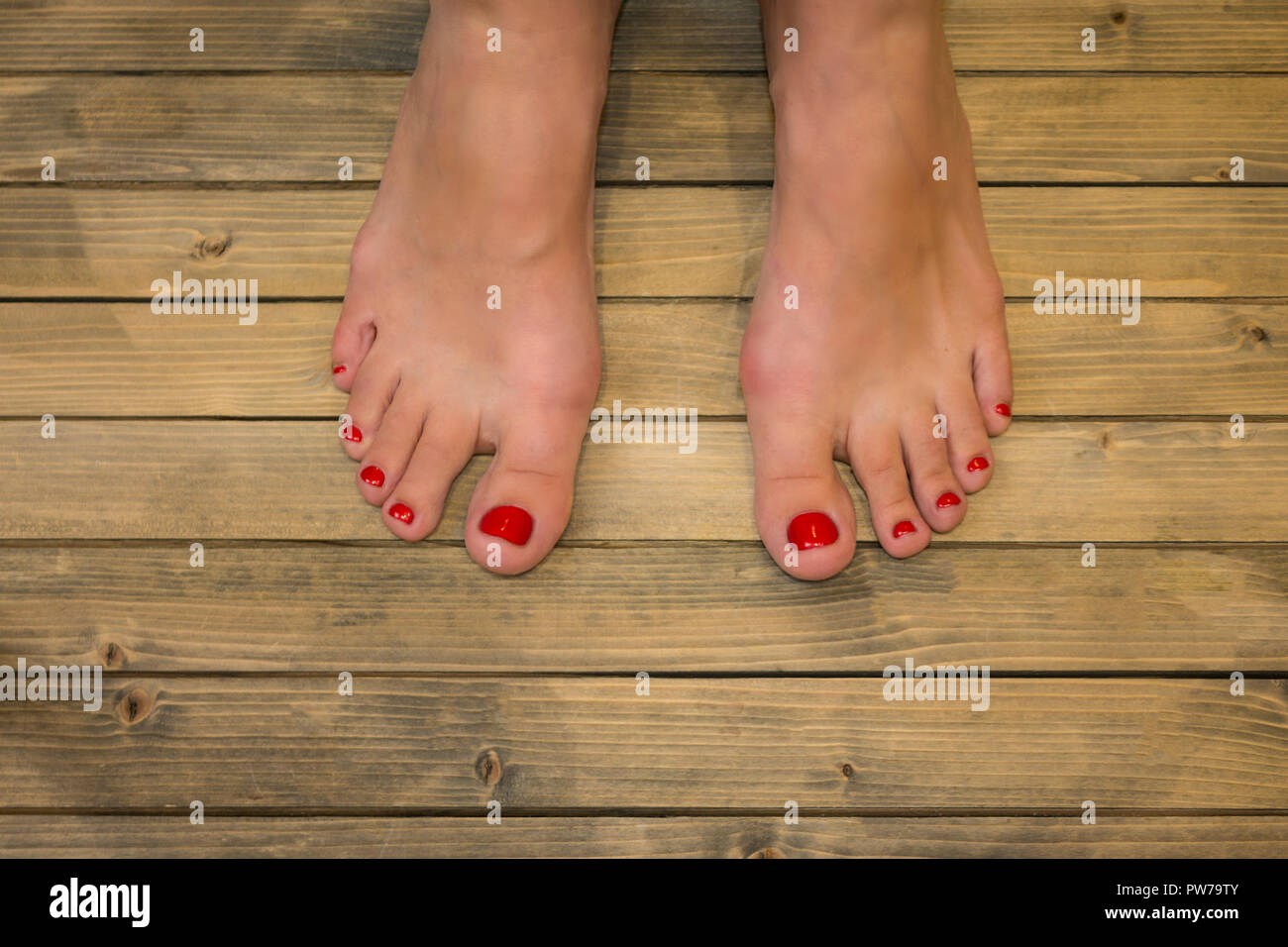 Female feet in on wooden floor or background - Stock Image