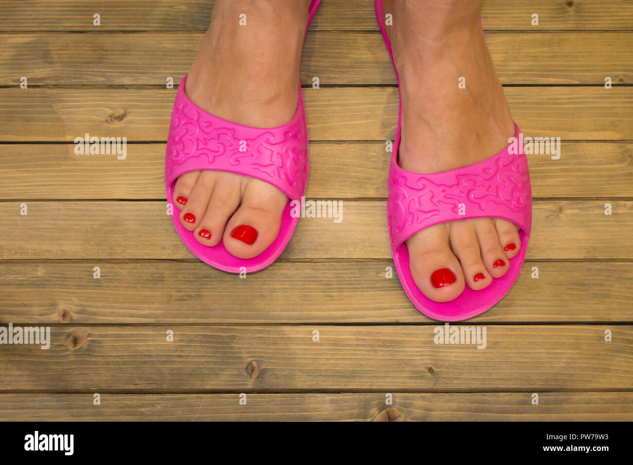 Female feet in slippers on wooden floor or background - Stock Image