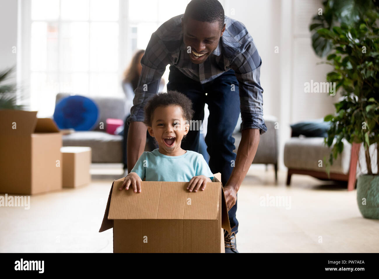 Black father and son playing with box at home - Stock Image