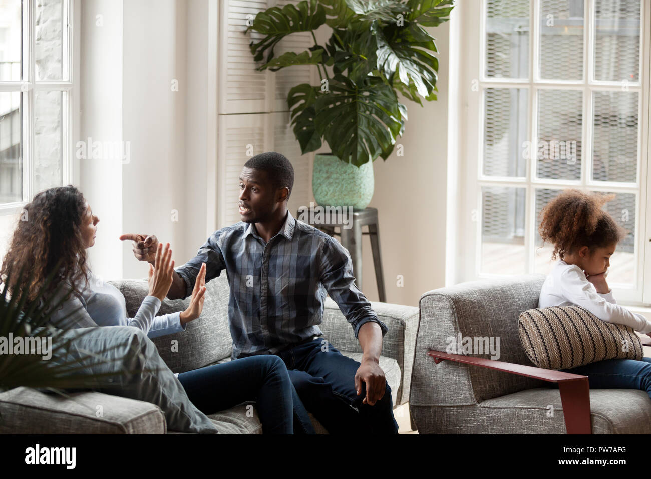 Unhappy family with kid quarrelling at home - Stock Image