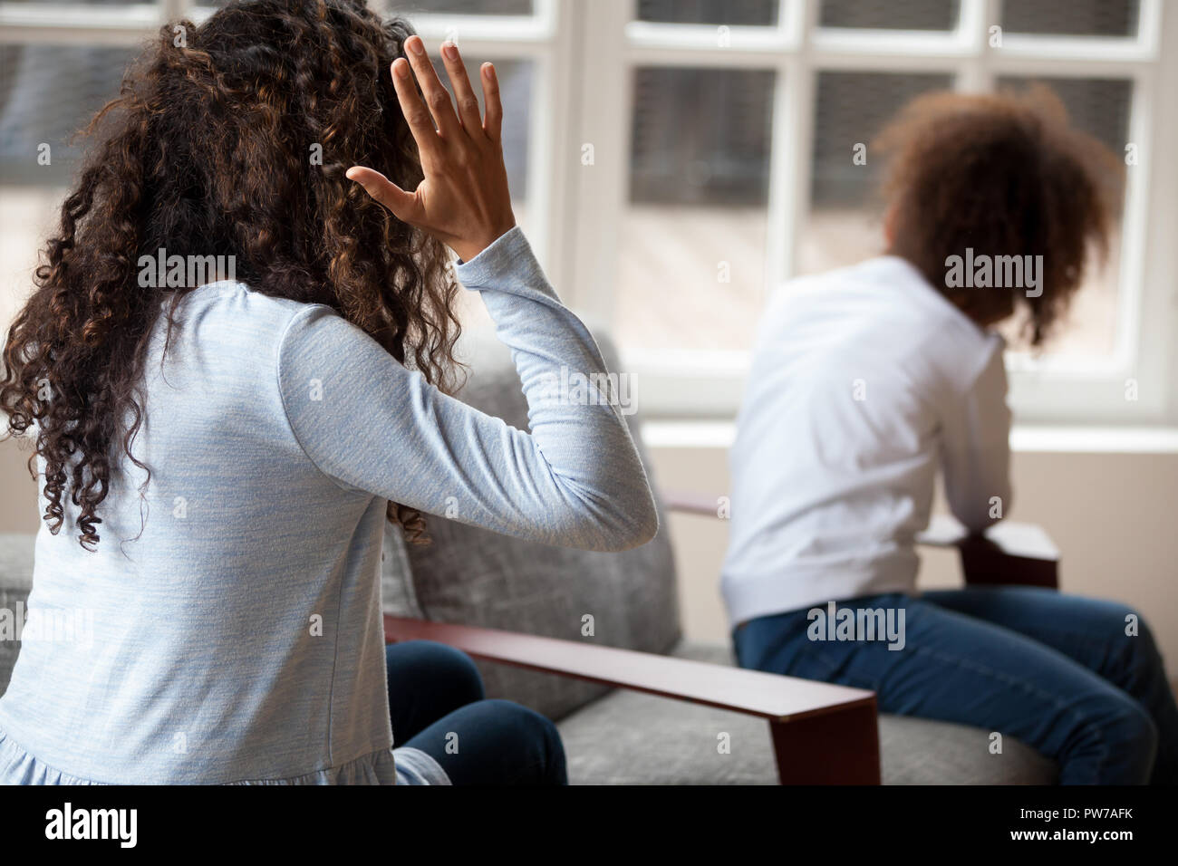 Rear view African mother quarrelling with daughter - Stock Image