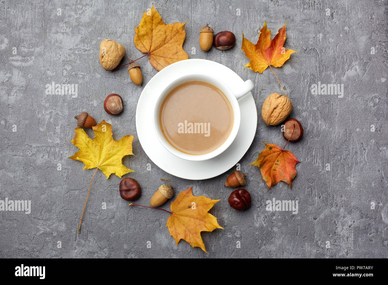 Autumn composition. Cup of coffee, autumn leaves on grey background. Flat lay. Stock Photo