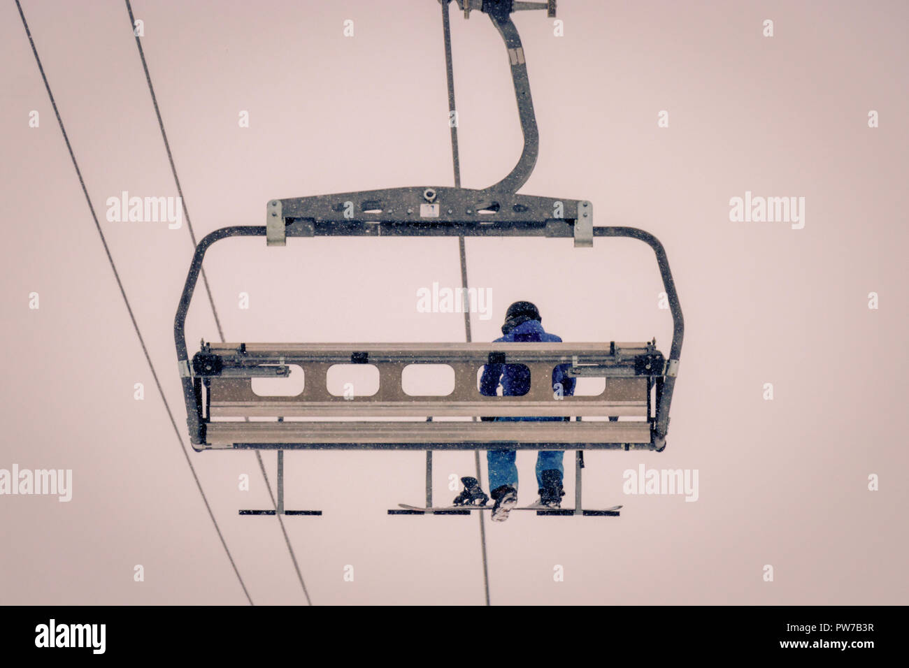 A lonely snowboarder sitting completely alone in a chairlift. Freezing cold foggy weather is making this ride extremely uncomfortable. Taken in Tignes Stock Photo