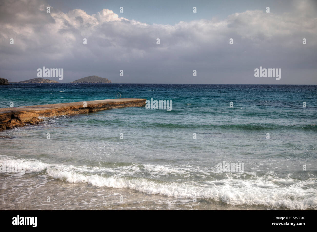 Winter seascape on the island of Syros with pier on the far left.Location village of Azolimnos in Syros, Greece. - Stock Image