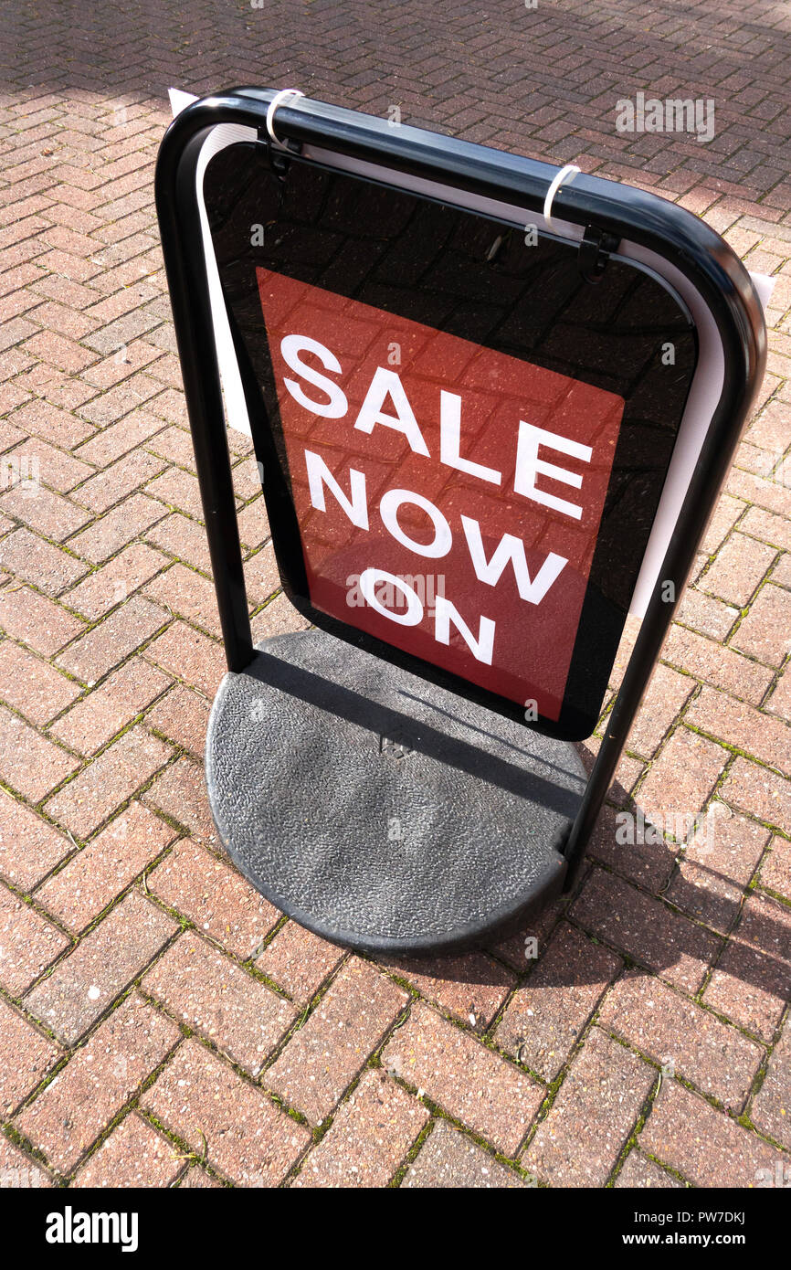 Sale now on swinging street sign - Stock Image