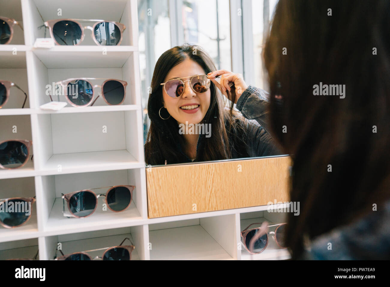 c824412207 attractive woman trying sunglasses in the glasses shop and looking in the  mirror. Asian lady