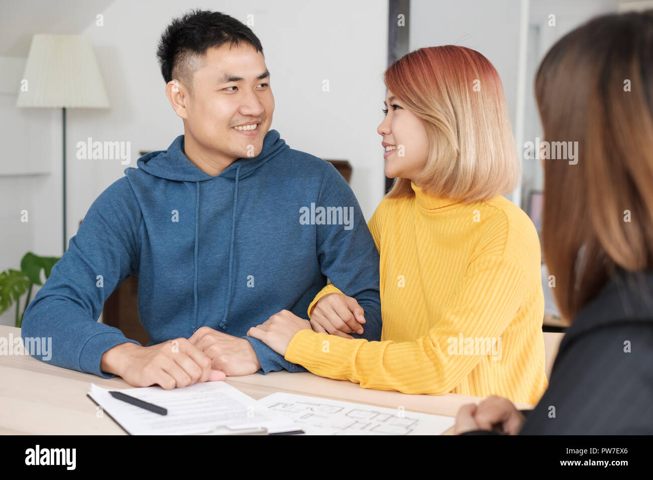 Asian happy couple buying new home with realtor agent with smiling face at new home.buying new house real estate Stock Photo