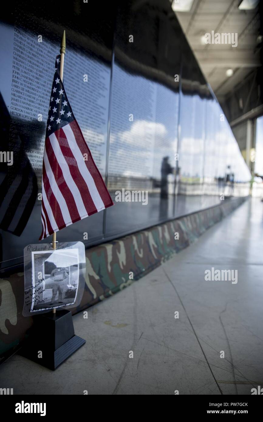 "A picture of Sgt. Richard Carter, a soldier who died during the Vietnam War, rests in front of the Mobile Vietnam Memorial Wall, also known as the AV Wall, during the 2017 Marine Corps Air Station Miramar Air Show at MCAS Miramar, Calif., Sept. 22. Carter's brother, Augie Anderson, is an AV Wall volunteer and placed the flag and photograph as a way to remember Carter, who died Nov. 19, 1967.  Anderson wrote ""Rest peacefully my brother, see you soon enough!"" - Stock Image"