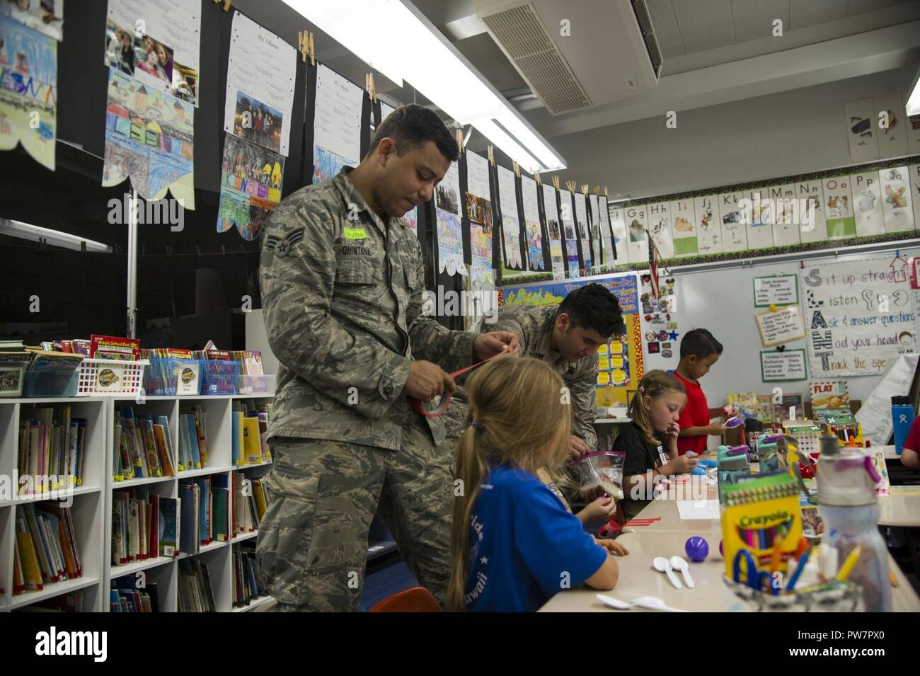 Senior Airman Francisco Quintana and Senior Airman Eddy Santibanez, 647th Logistics Readiness Squadron combat mobility team members, help second grade students make maracas at Hickam Elementary School, Joint Base Pearl Harbor-Hickam, Hawaii, Sept. 27, 2017.  Volunteers organized a variety of events for the students in support of Hispanic Heritage Month.  Hispanic Heritage Month is observed from 15 Sept.-15 Oct. to celebrate the history, culture and contributions of American citizens whose ancestors came from Spain, Mexico, the Caribbean and Central and South America. - Stock Image