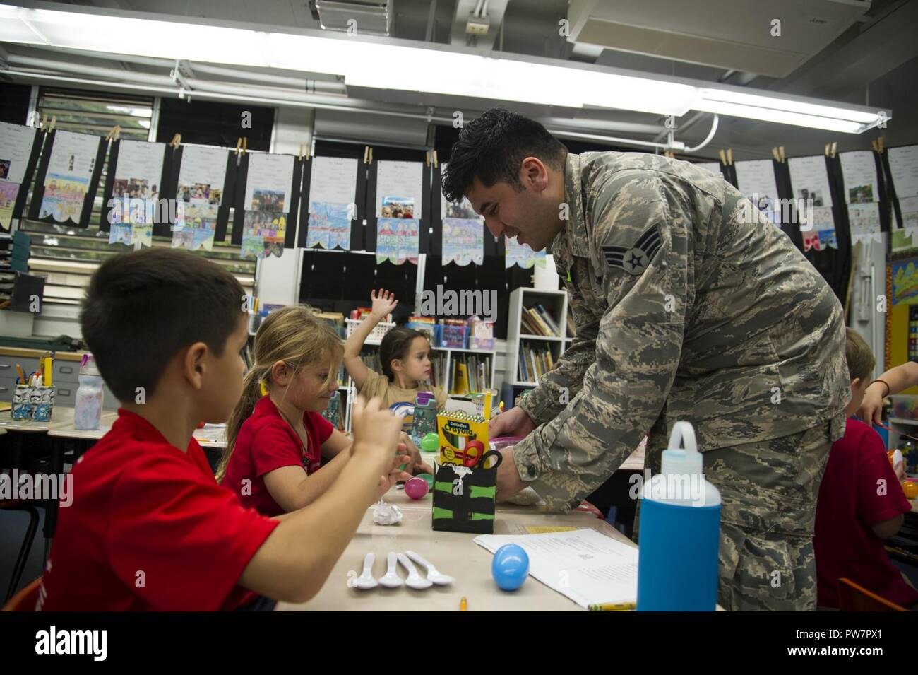Senior Airman Eddy Santibanez, 647th Logistics Readiness Squadron combat mobility team member, helps second grade students make maracas at Hickam Elementary School, Joint Base Pearl Harbor-Hickam, Hawaii, Sept. 27, 2017.  Volunteers organized a variety of events for the students in support of Hispanic Heritage Month.  Hispanic Heritage Month is observed from 15 Sept.-15 Oct. to celebrate the history, culture and contributions of American citizens whose ancestors came from Spain, Mexico, the Caribbean and Central and South America. - Stock Image