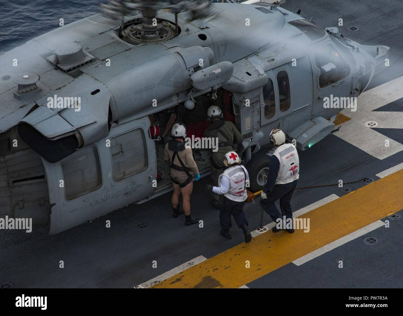 CARIBBEAN SEA (Sept. 28, 2017) Sailors escort a rescued resident of French Guadalupe on the flight deck of the amphibious assault ship USS Wasp (LHD 1) following a search and rescue (SAR) mission for a private aircraft off the coast of the island Dominica. Wasp is currently participating in humanitarian relief efforts on Dominica following the landfall of Hurricane Maria. The Department of Defense is supporting the United States Agency for International Development (USAID), the lead federal agency, in helping those affected by Hurricane Maria to minimize suffering and is one component of the o Stock Photo