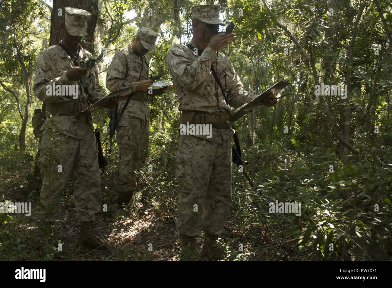 U.S. Marine Corps Recruits with Delta Company, 1st Battalion, Recruit Training Regiment, use compass techniques to reach their next plot point at Elliot's Beach on Marine Corps Recruit Depot, Parris Island, S.C., Sept. 25, 2017.  The Land Navigation Course teaches recruits how to properly navigate unfamiliar terrain. Stock Photo