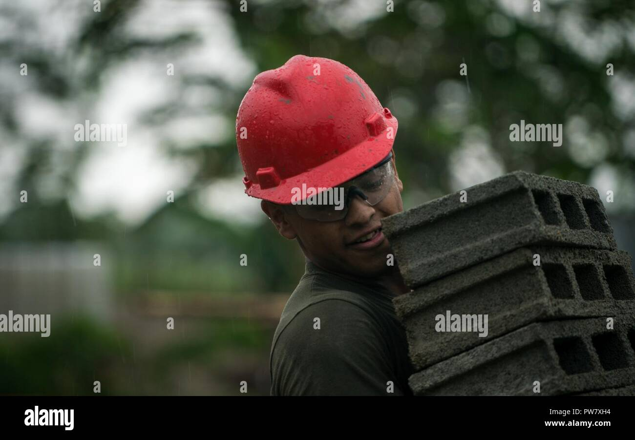 U.S. Marine Pfc. Fernando Dominguez carries concrete blocks to protect them from the rain at Esperanza Elementary School in support of KAMANDAG in Casiguran, Aurora, Philippines, Sept. 30, 2017. KAMANDAG helps maintain a high level of readiness and enhances bilateral military relations and capabilities. Dominguez is a combat engineer with Bravo Company, 9th Engineering Support Battalion, 3rd Marine Logistics Group, and is a native of Las Vegas, Nevada. Stock Photo