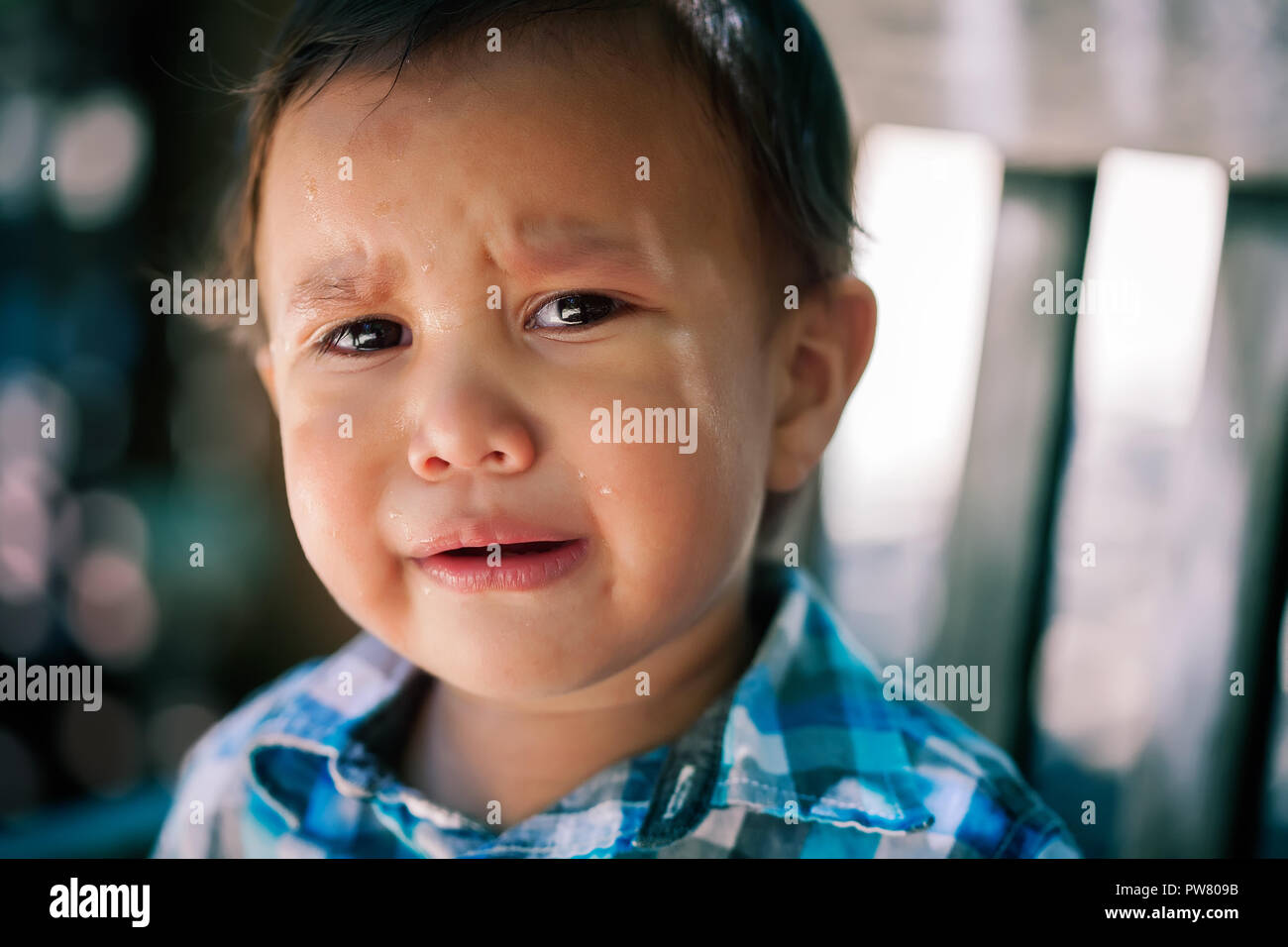 Young latino son, toddler age crying with tears in eyes looking lost or worried  with menacing looking background, expressing missing or hurt children - Stock Image