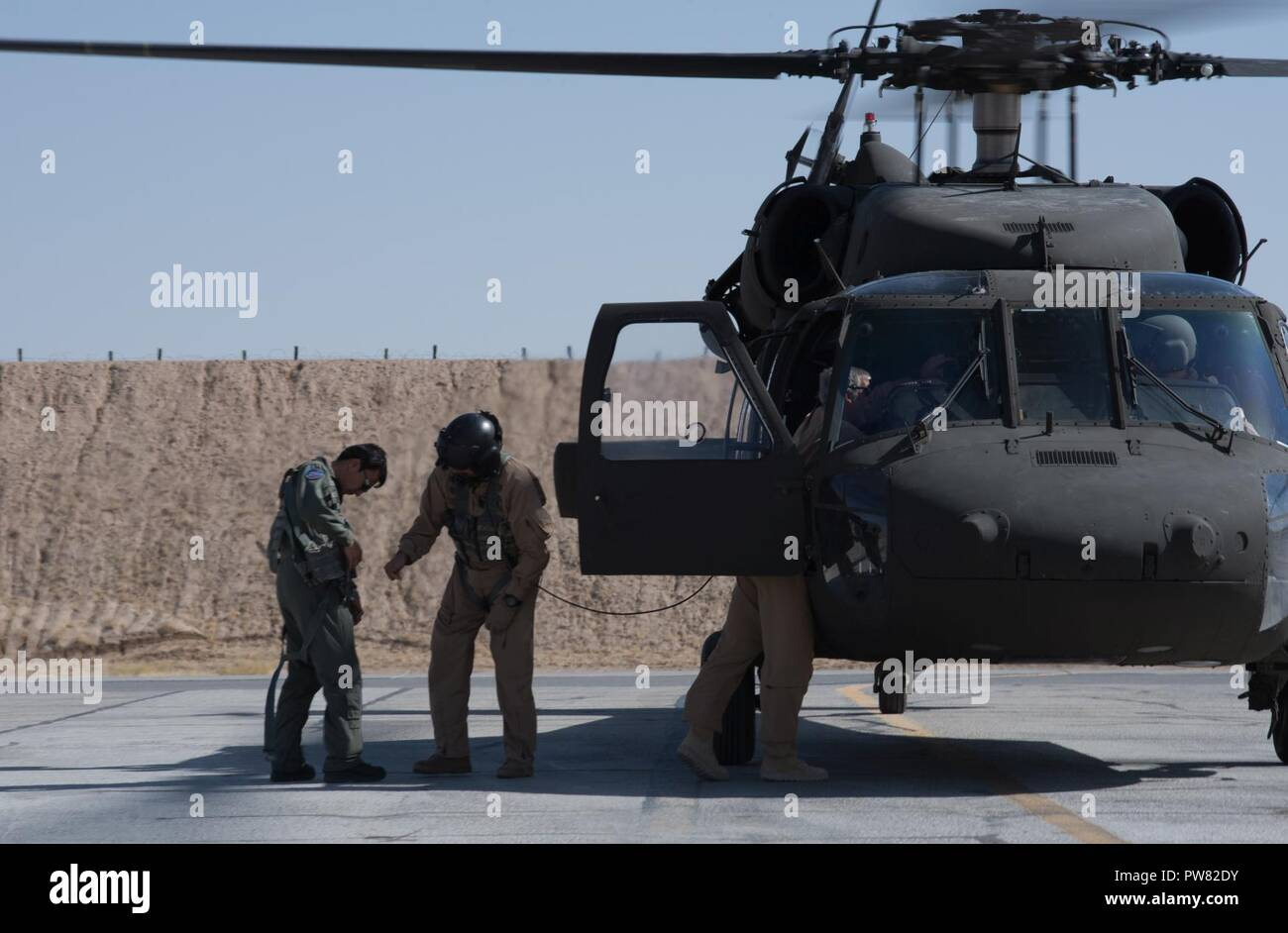 us instructor pilots assist an afghan mi 17 pilot into a safety harness before his first orientation flight in the afghan uh 60a black hawk oct 3 2017 at kandahar airfield afghanistan mi 17 pilots are retraining to the black hawk and are expected to fly the aircraft by the end of 2017 the uh 60 is part of a multi year modernization plan for the afghan air force PW82DY u s instructor pilots assist an afghan mi 17 pilot into a safety